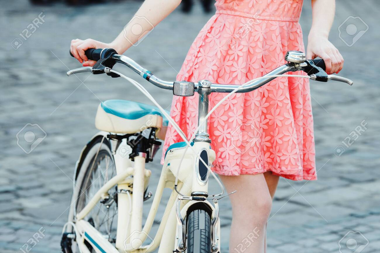 girl with bicycle on the street with retro bicycle - 122488763