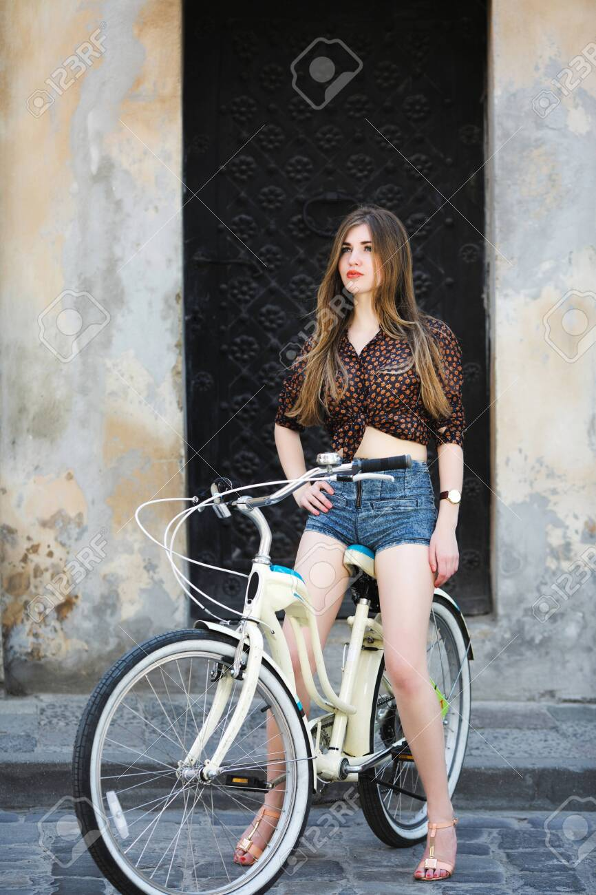 Pretty girl is sitting on bicycle on the street of old city - 122488766