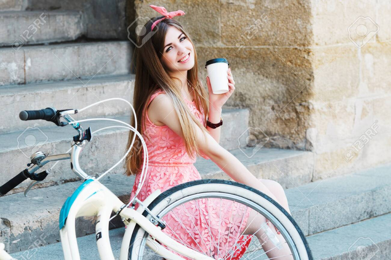 girl smiling with a cup of coffee and vintage bicycle - 122488772