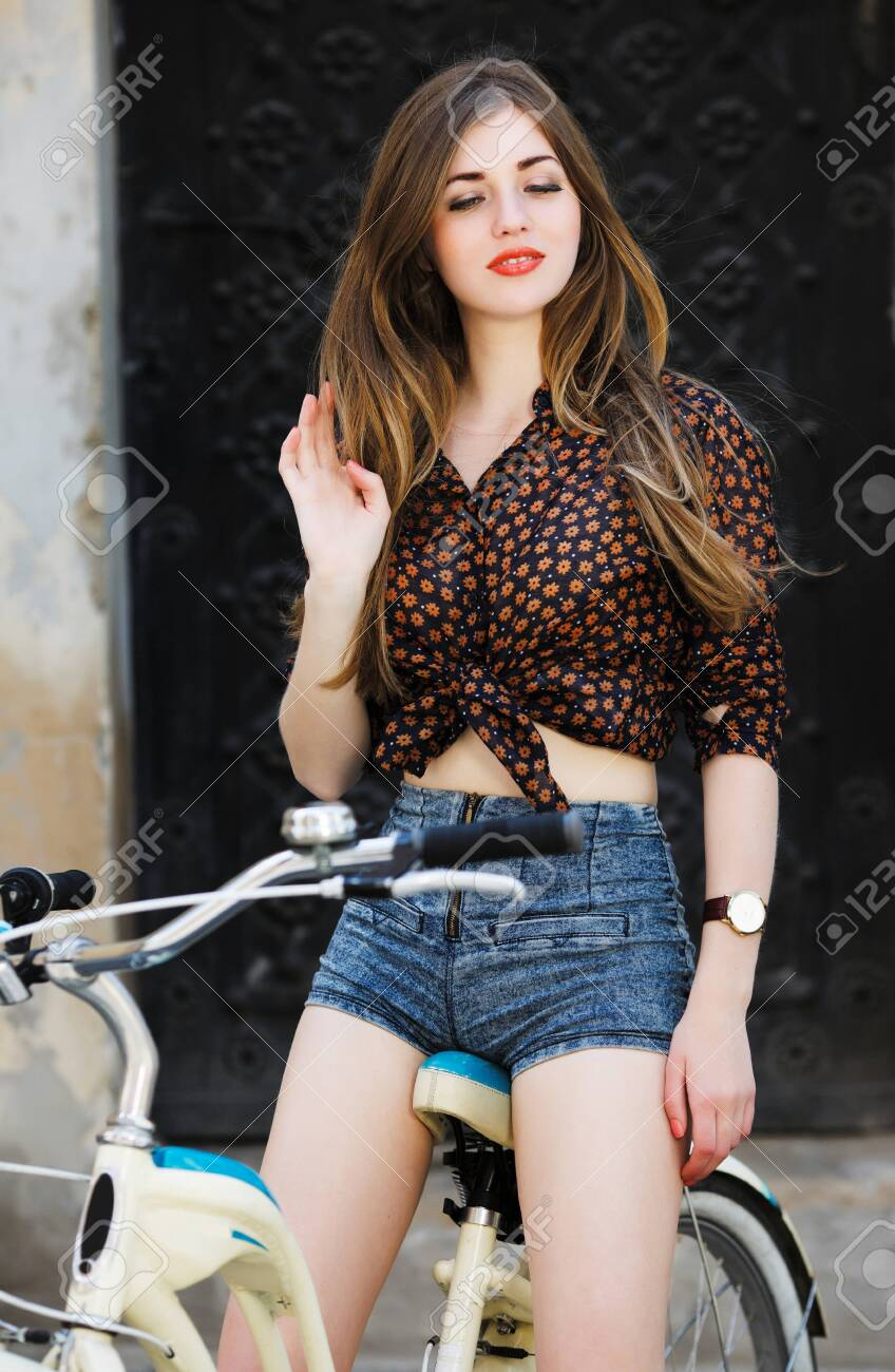 Cute girl with long hair is posing on bicycle on the street - 122491599