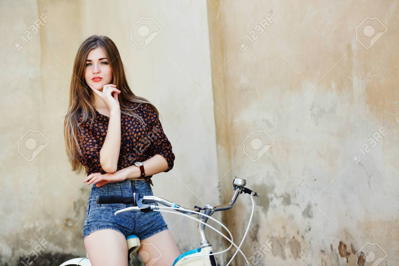 Nice girl with long hair is posing on the bicycle on the old wall background - 122491601