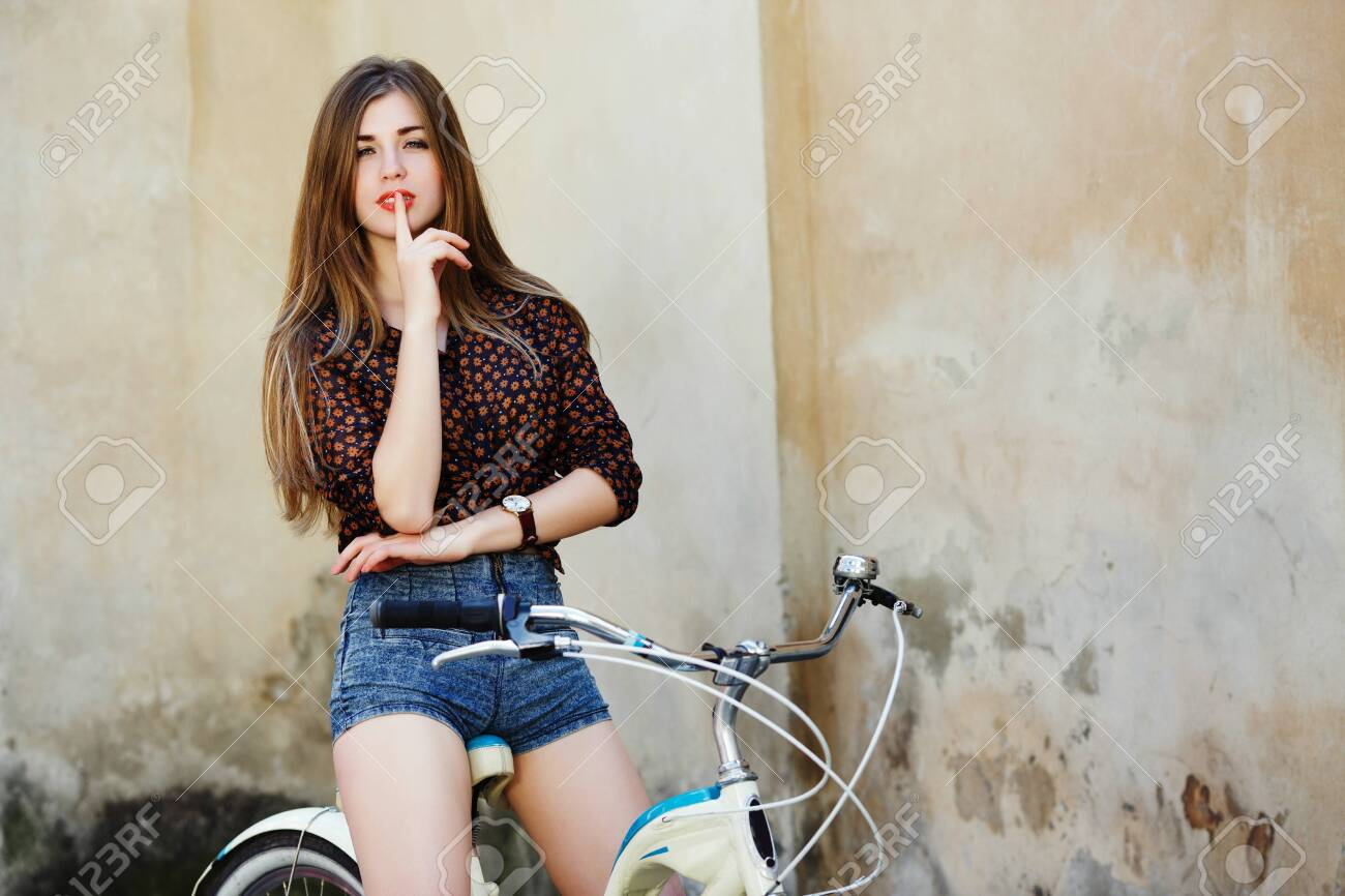 Passionate young woman with long hair is posing on the bicycle on the old wall background - 122488802