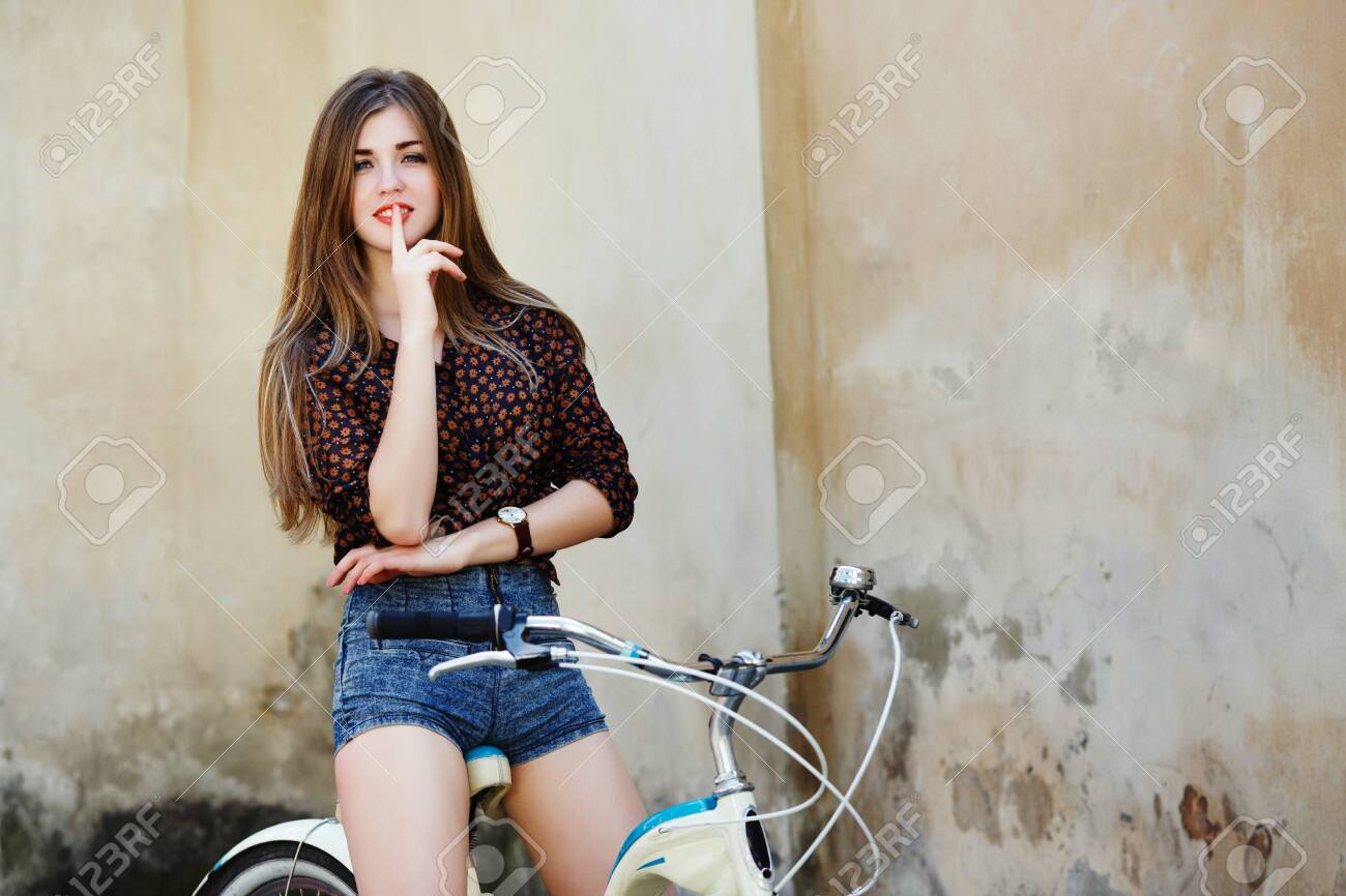 Smiling young woman with long hair is posing on the bicycle on the old wall background - 122488804