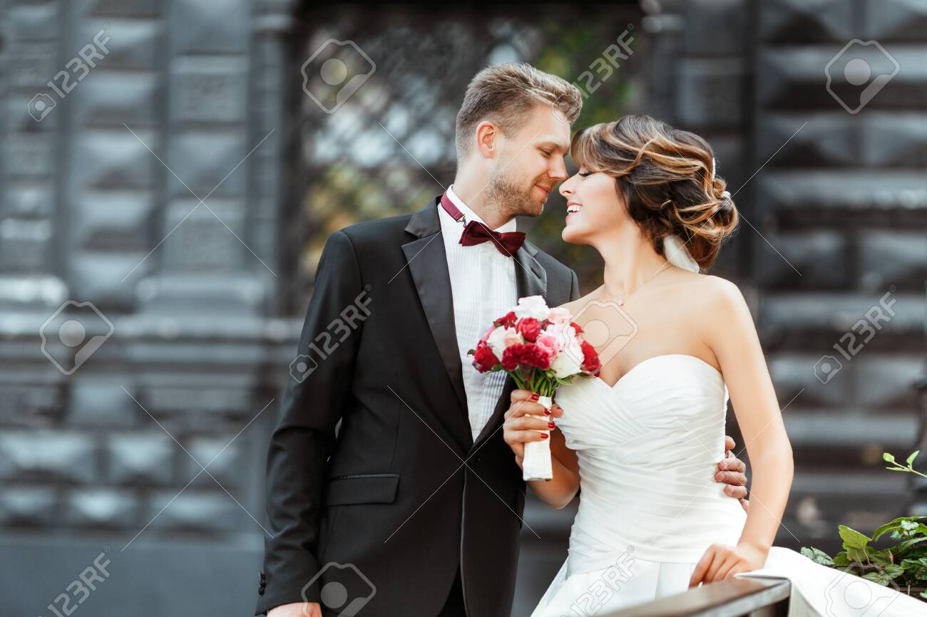 Bride and bridegroom standing with bouquet and smiling - 122381118