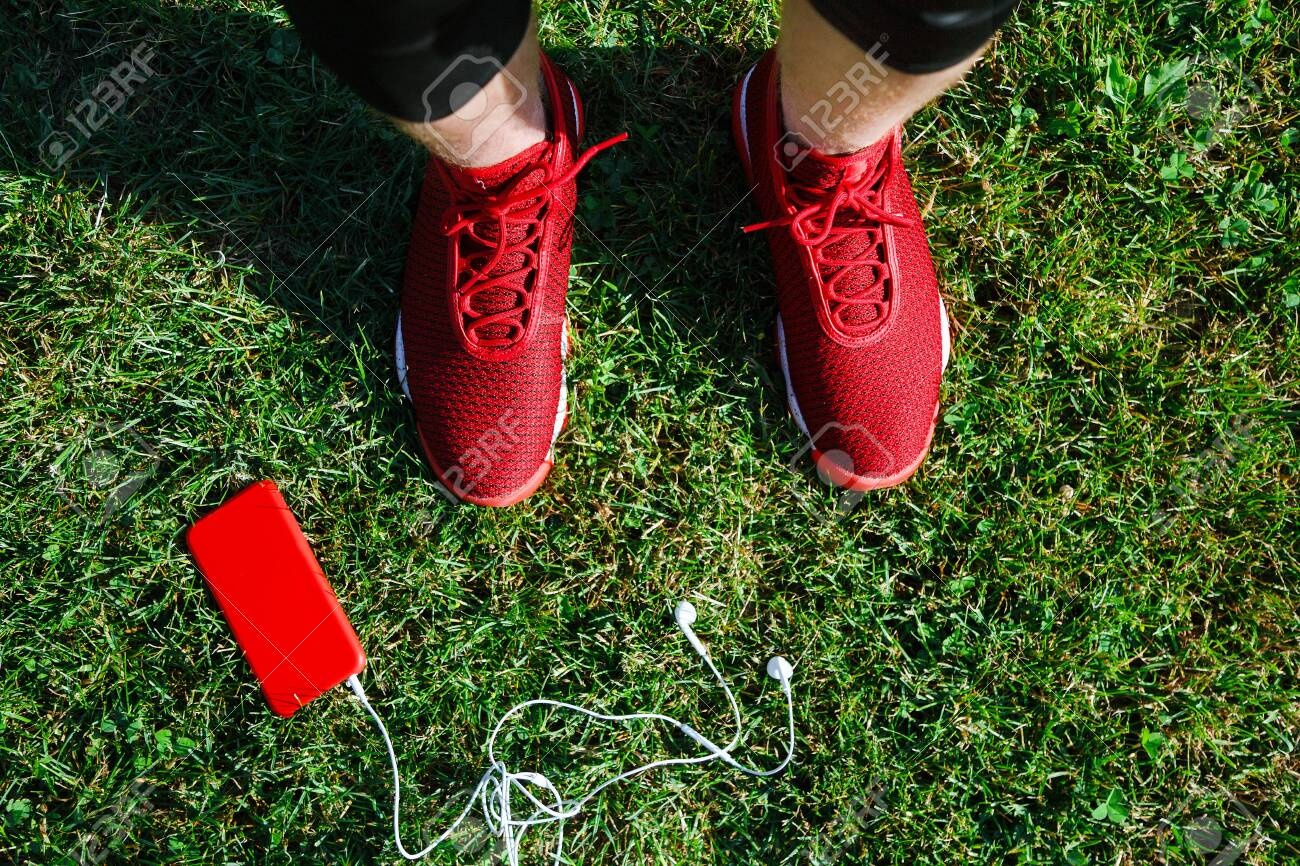 Red sneakers, phone on grass - 122488826