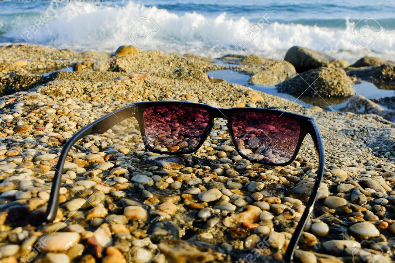 Black sunglasses at sea background - 122488829