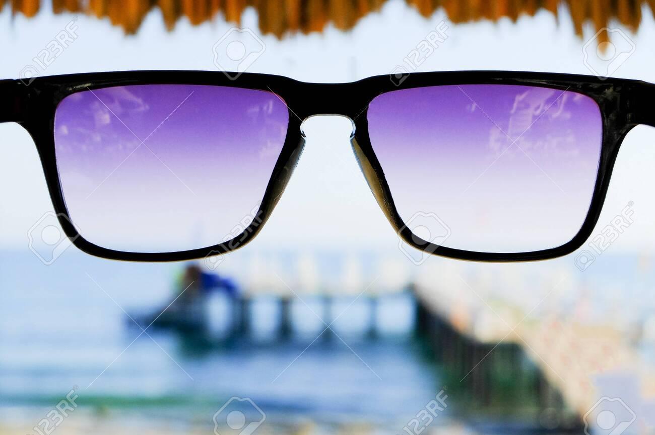 Black sunglasses at sea background - 122488831