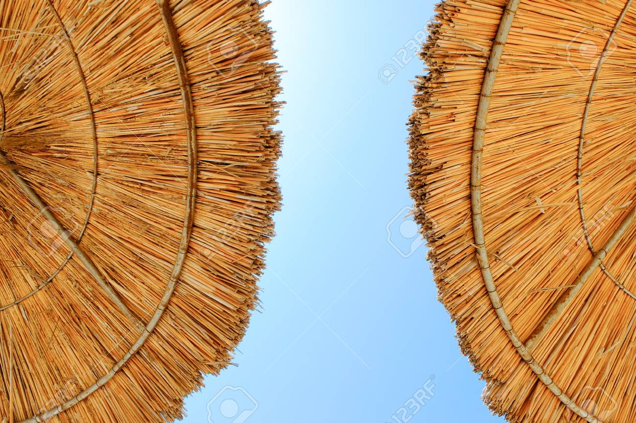 Beach umbrellas made of straw at blue sky background - 122493985