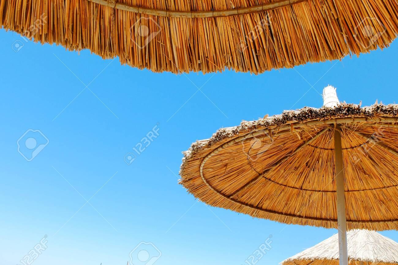 Three beach umbrellas made of straw at blue sky background - 122493986