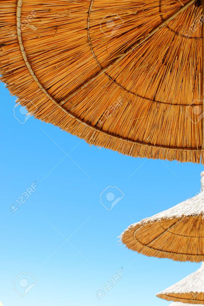 Beach umbrellas made of straw at blue sky background - 122493988