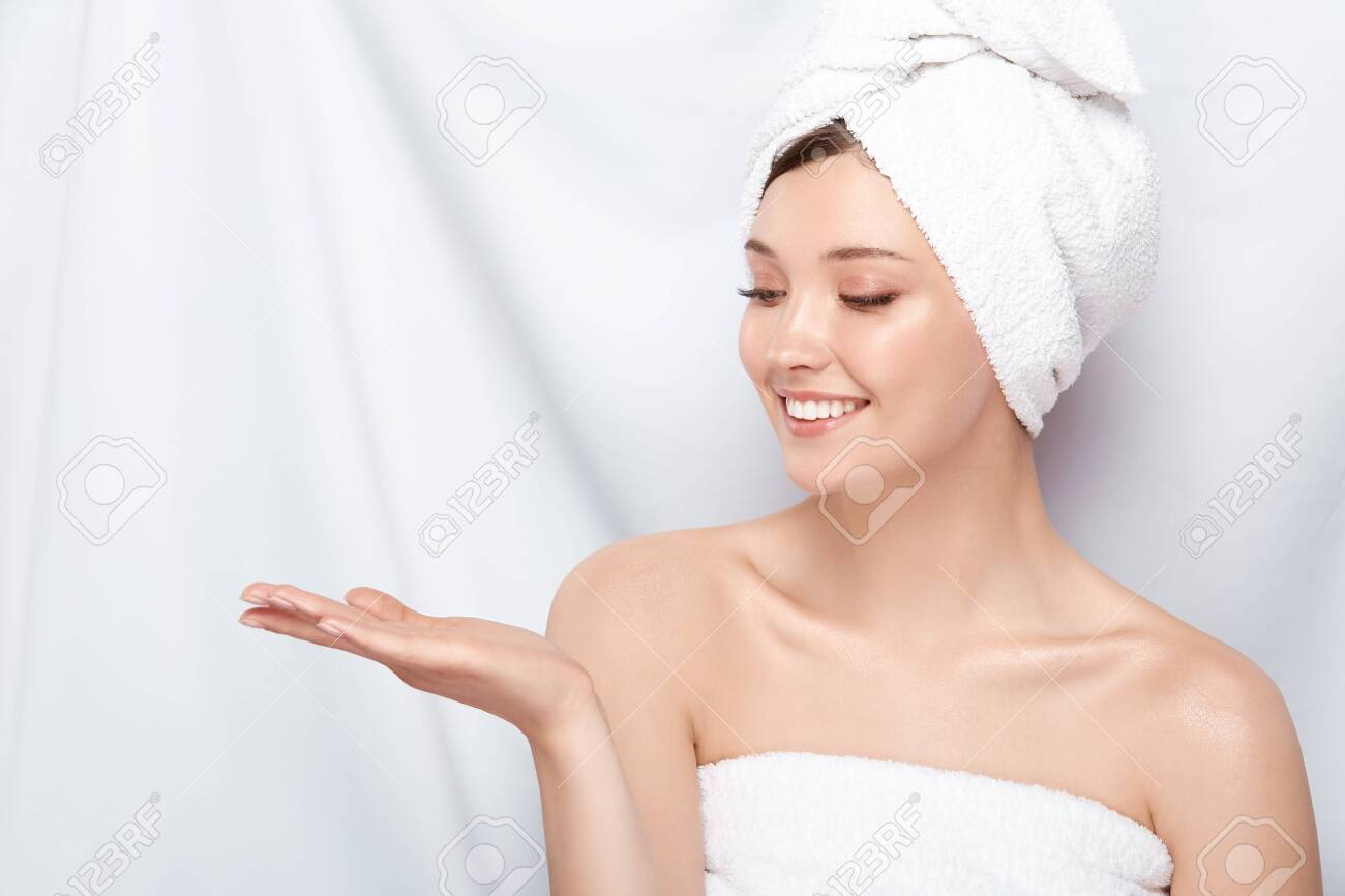 beautiful girl with perfect skin and in bath towel looking to her hand, copy space, young and fresh natural face after spa - 123710866