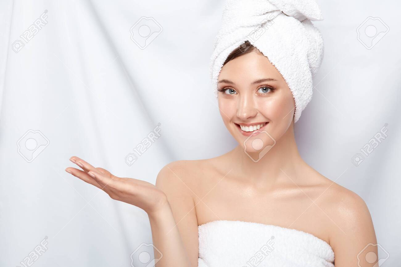 attractive young lady in bath towel on head pretending that she holding something on her arm, copy space, pretty girl keeps arm near shoulder - 123710964