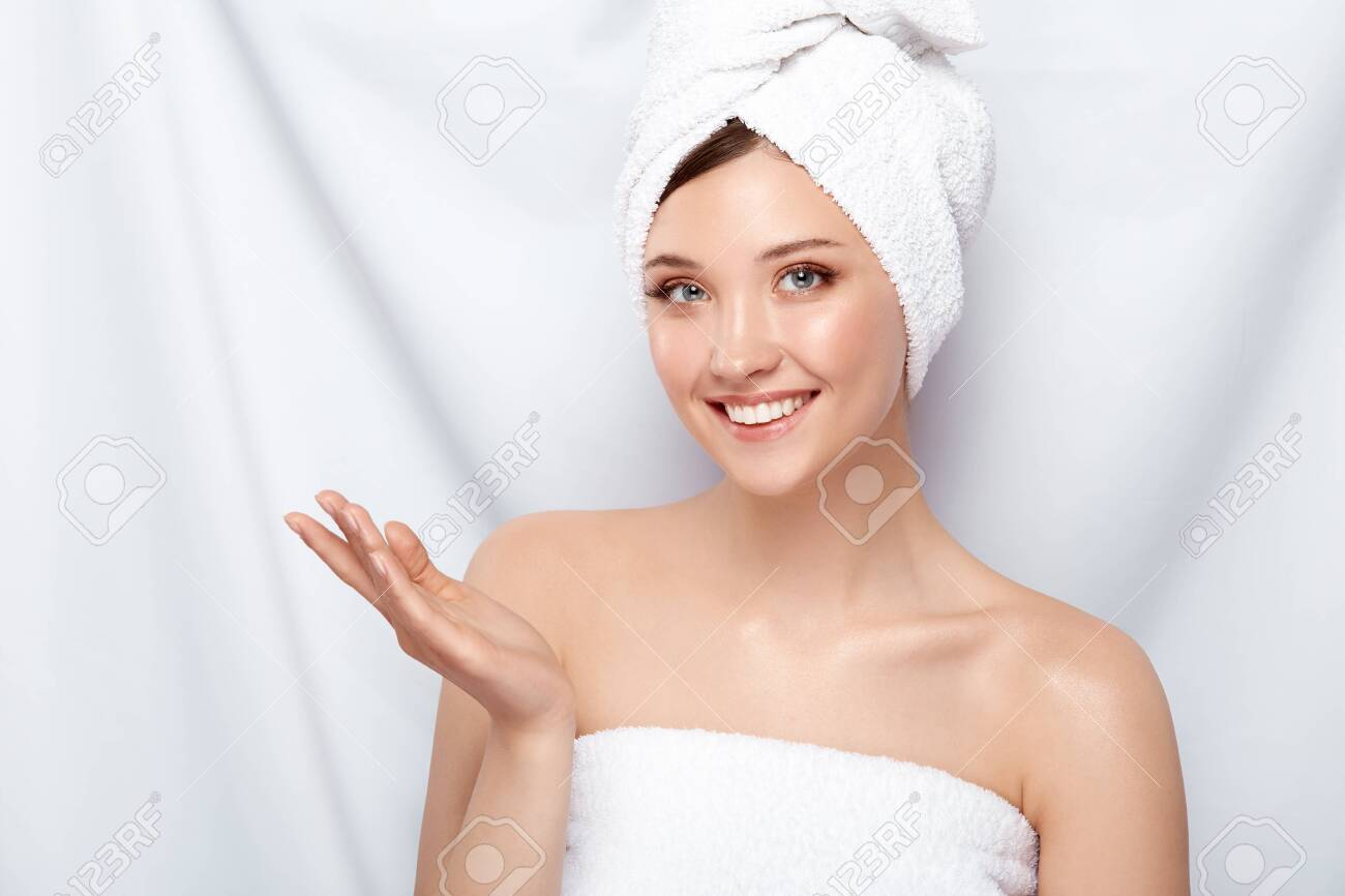 pretty girl with perfect smile in bath towel looking to the camera and holding her hand, copy space, spa and facecare treatment - 123710966