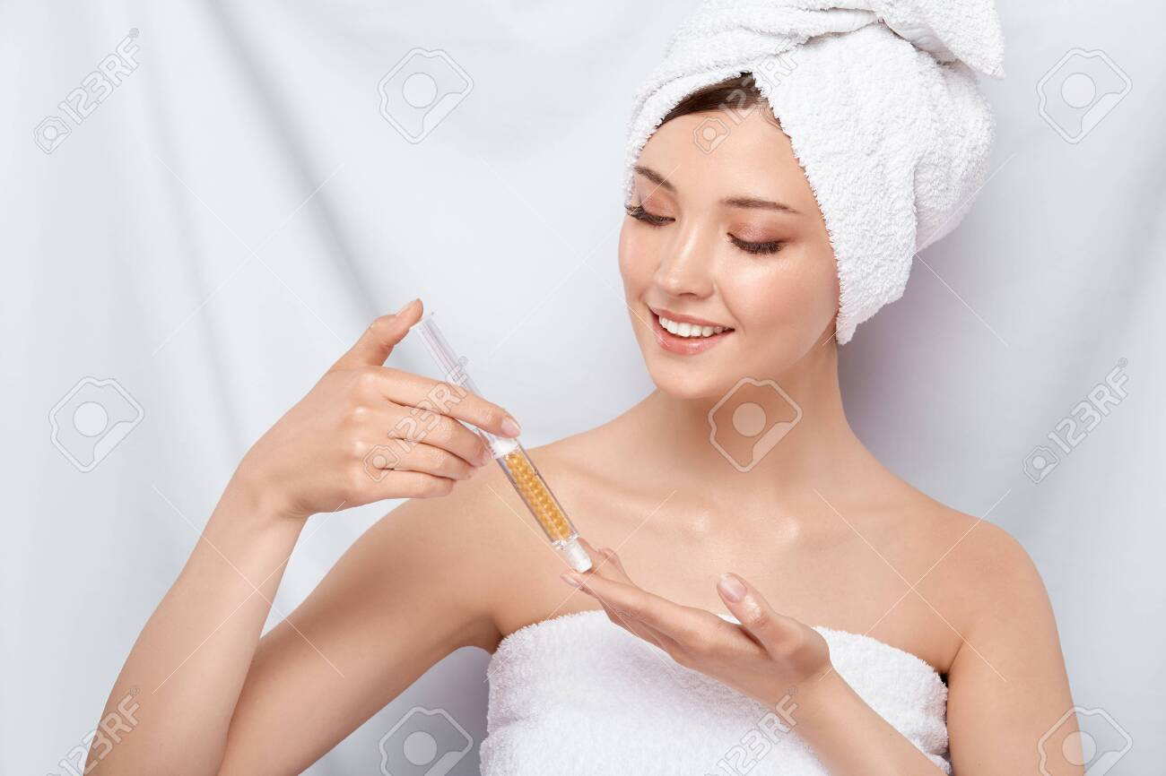pretty woman in bath towel on her head holding beauty injection and looking on it with smile, face treatment - 123711125