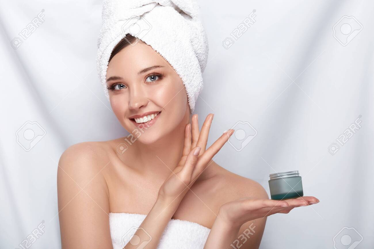 beautiful girl in bath towel on her head holding cream and touching her face on white,facial treatment with perfect skin lady - 123711195