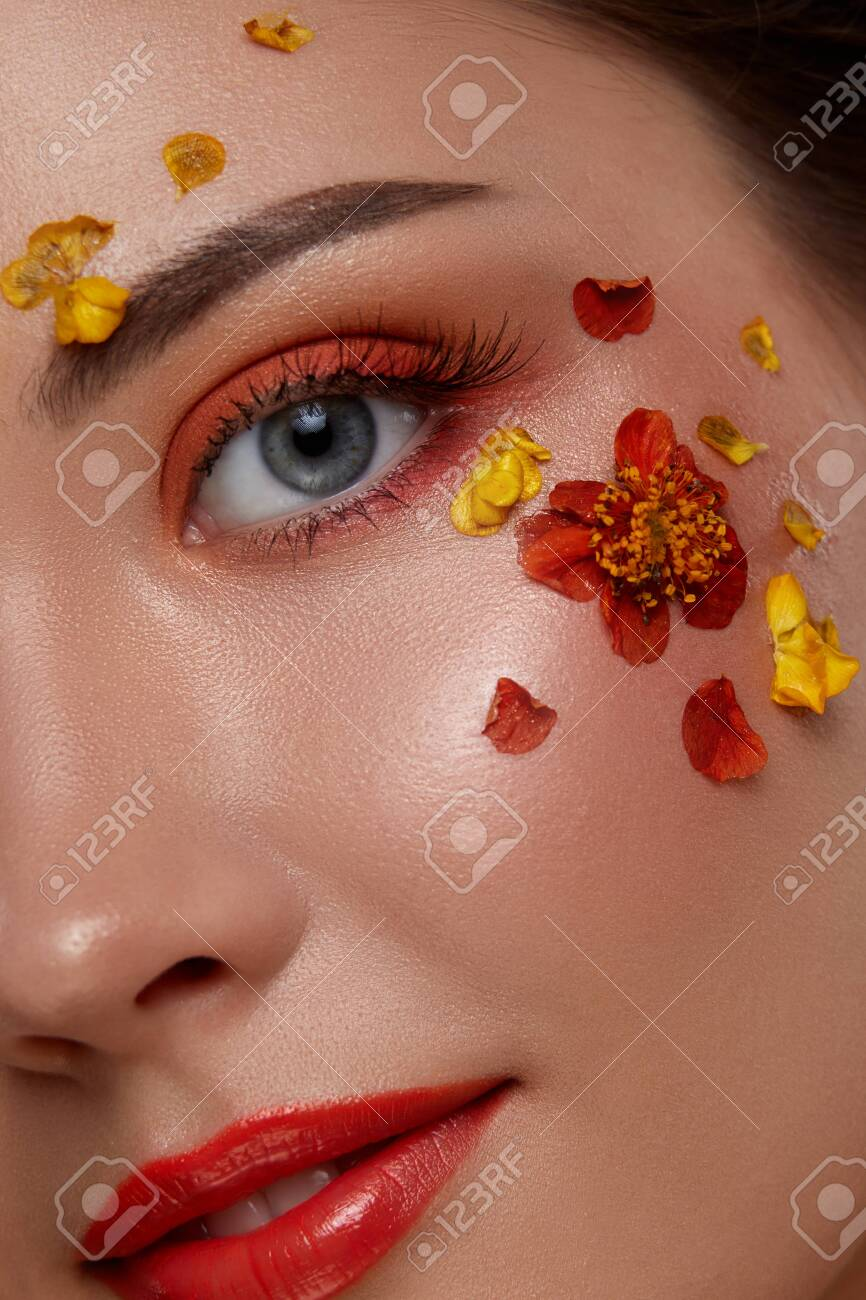 beautiful woman face looking to the camera with colorful make-up and flowers on it, gorgeous flowered orange mua - 125643756