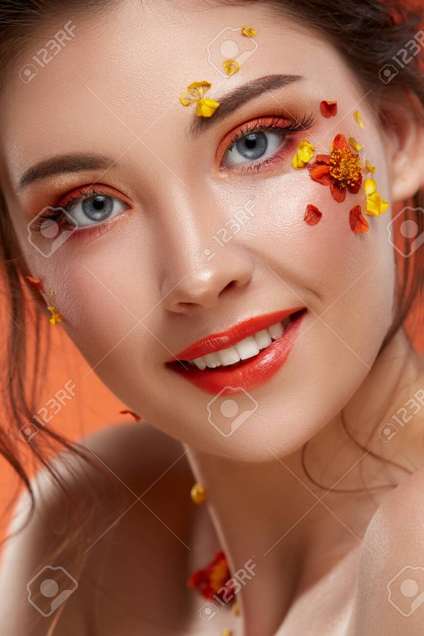 close-up portrait of pretty girl with orange make up and flowers on her face looking to the camera, fashion beauty - 125643758