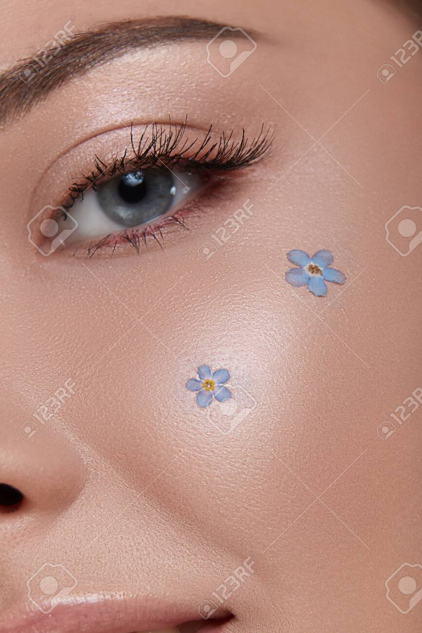 woman eye with perfect make-up and forget-me-nots on the cheek, close-up of girl face wih blue flowers - 129213761