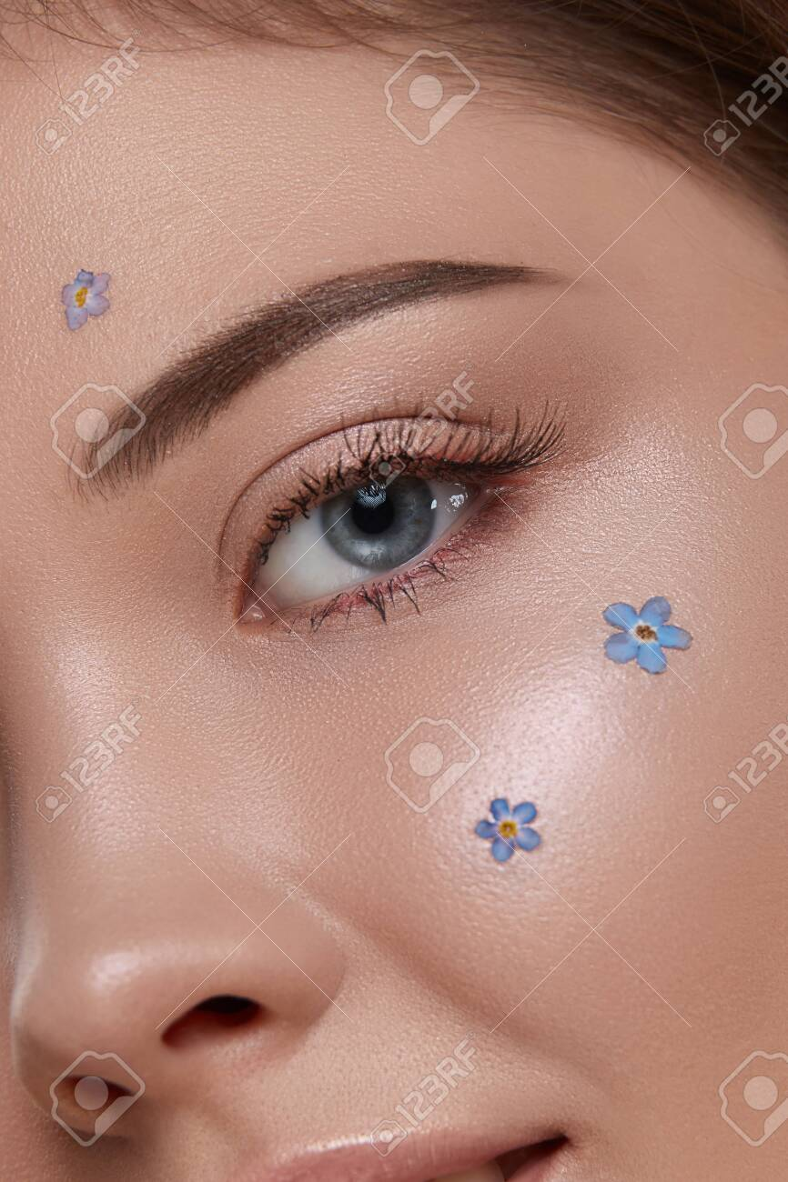 romantic woman's eye looking to the camera with fresh blue flowers on cheek, close-up of woman face with forget-me-nots and shiny mua - 129213782