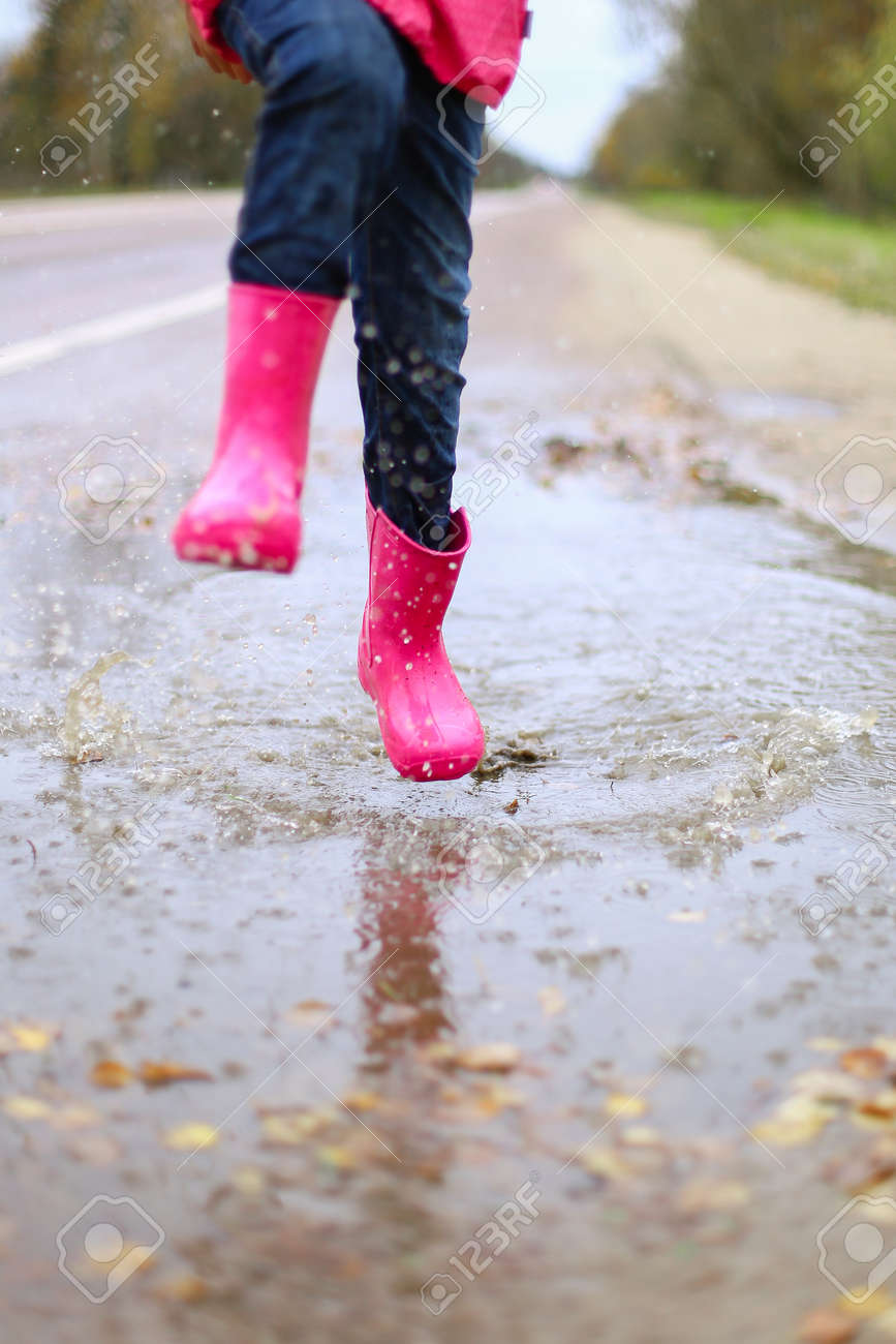 Happy little girl in pink waterproof jacket, rubber boots cheerfully jumps through puddles on street road in rainy weather. Spring, autumn. Children's fun in fresh air after rain. Outdoors recreation. - 144551724
