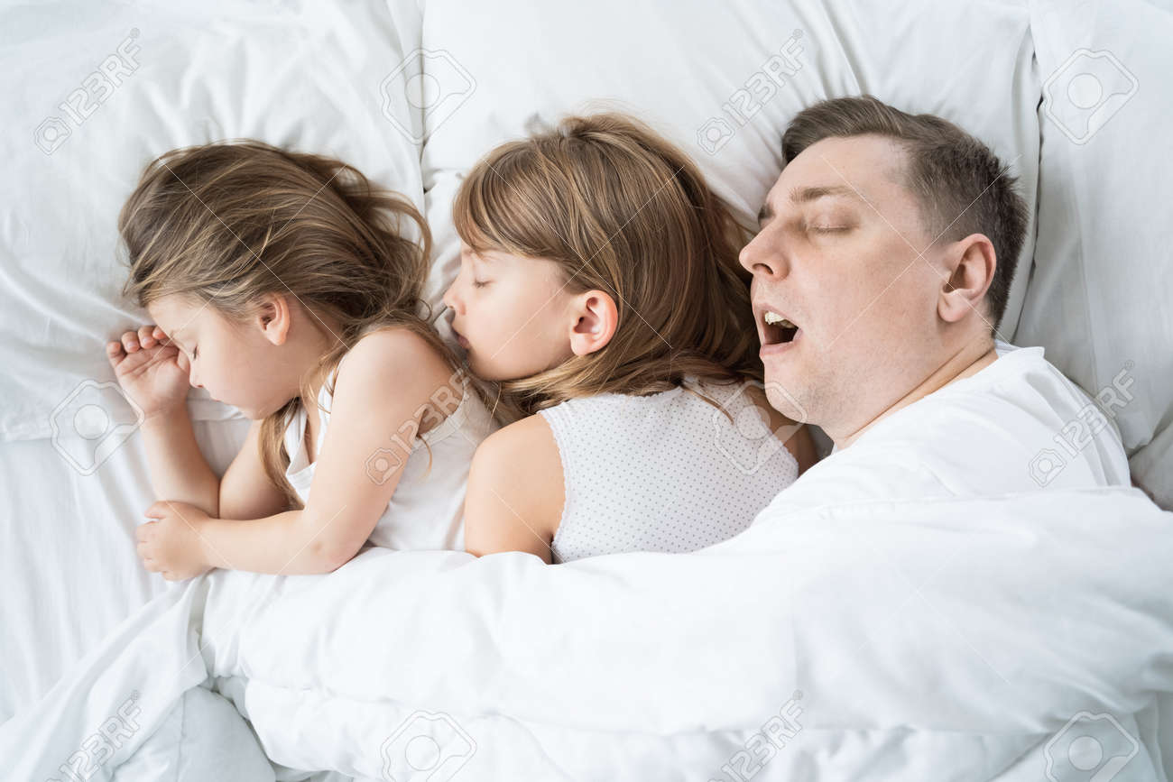 Kids, daughters, dad sleep together in bed on pillows under blanket. Father is snoring hard. Family joint sleeping. Insomnia, night bedtime. Sweet dreams. arly wake up, rise to kindergarten, school, work. - 157678009