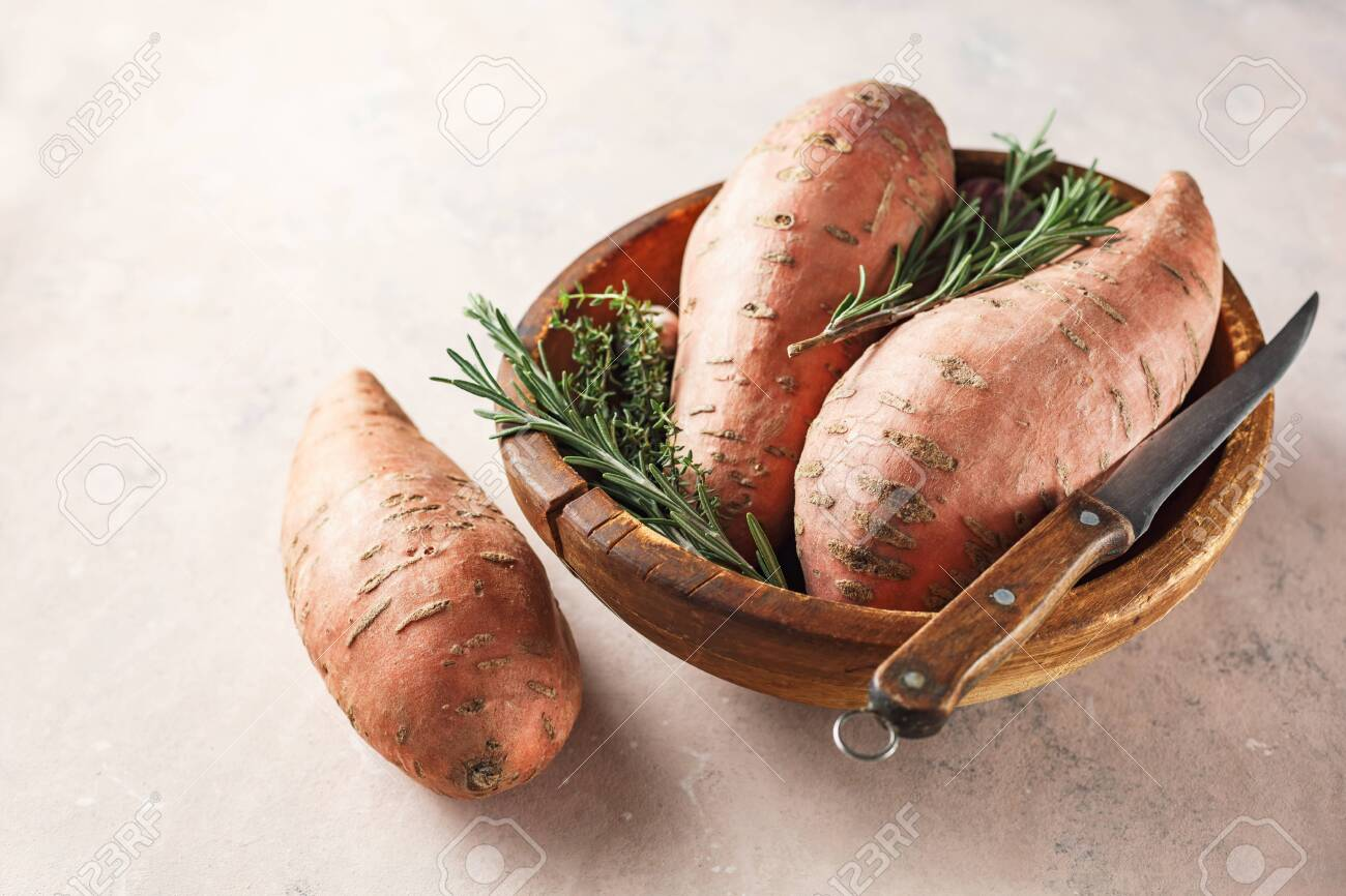 Organic sweet potatoes in a wooden bowl - 129402907