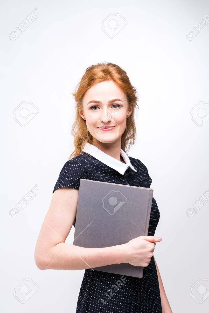 f6824520dbaed4 Mooi meisje met rood haar en grijze boek in handen gekleed in zwarte jurk  op witte