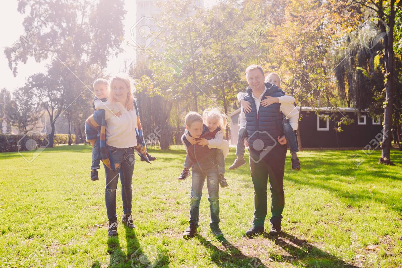 Theme family active leisure outside in nature. large Caucasian family with four children. Mom and Dad actively relaxing. enjoy life in park near house on grass. Children on back shoulders roll on top. - 120073943