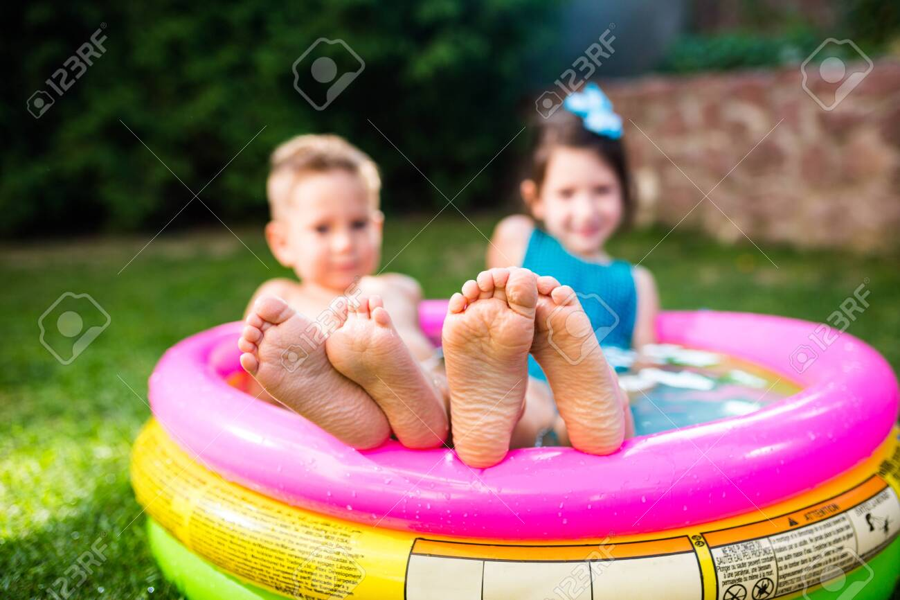 Theme summer vacation. Two children Caucasian brother and sister lie in water, inflatable home round pool in yard on green grass. Close-up of feet sole heels children in hot summer weather. - 152642566