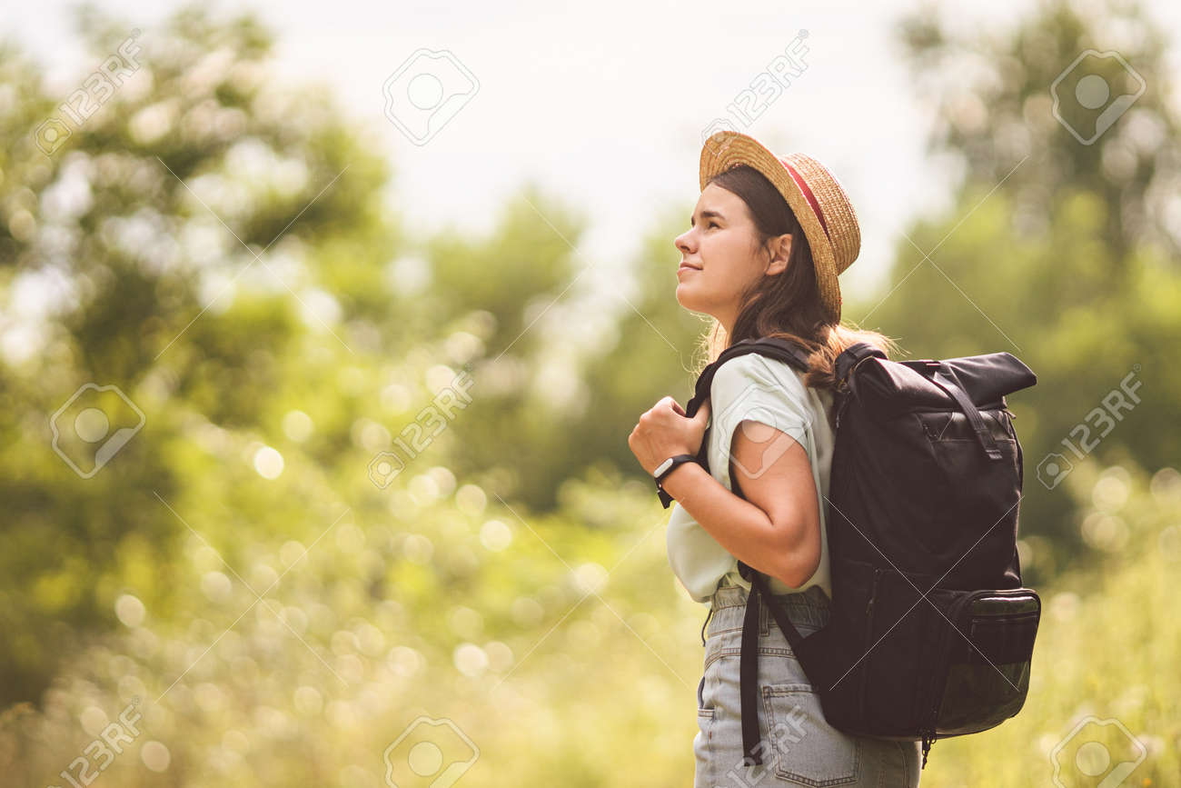 Stylish fashionable hipster traveler woman in hat with brim and roll top type backpack walking in nature. Travel and wanderlust concept. Exploring nature, hot summer day. Outdoor activity. Wanderlust. - 152734226