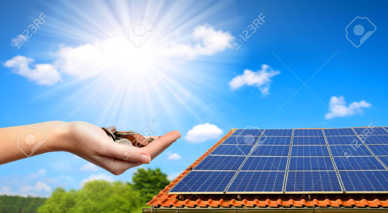 Solar panel on the roof of the house and coins in hand. The concept of money saving and clean energy. - 88570932