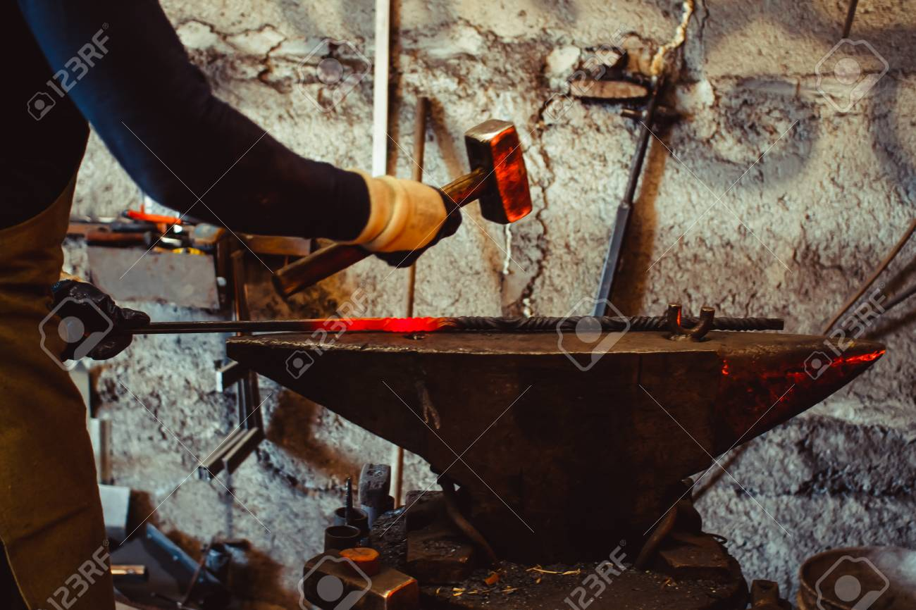 A blacksmith forging a horseshoe with a hammer onto anvil at