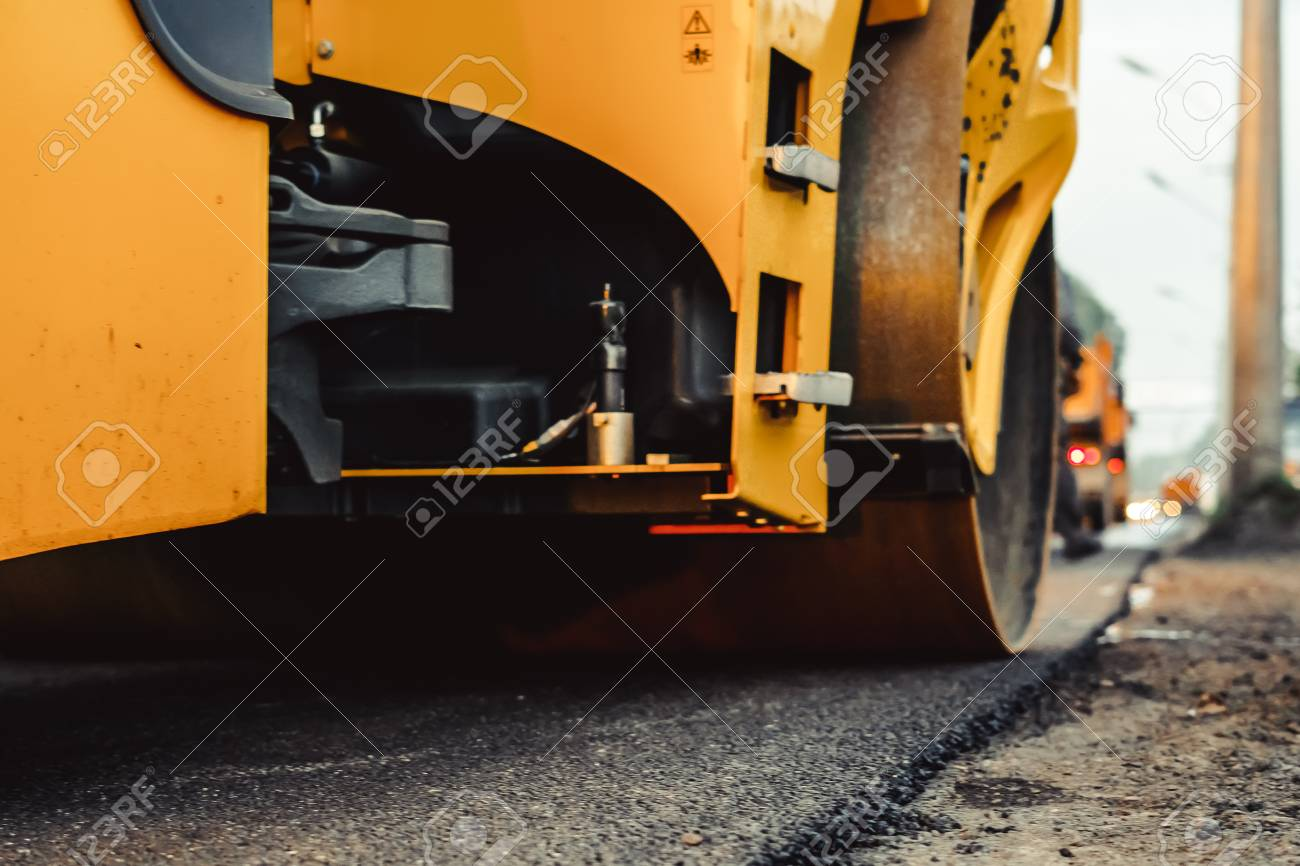 Road construction works with roller compactor machine and asphalt finisher - 105065740