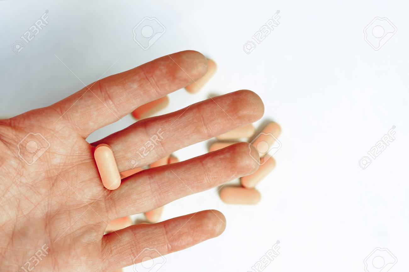 Top view of the pills on the hand and white background, A hand hold the pills and drug, Pile of the drug and pills on the hand. - 122264505