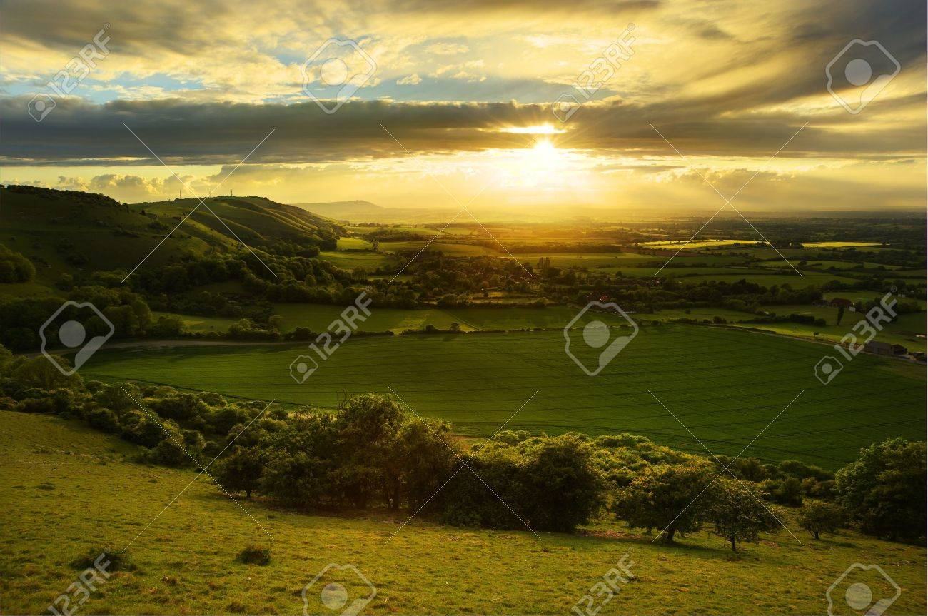 Lovely landscape of countryside hills and valleys with setting sun lighting up side of hills whit sun beams through dramatic clouds Stock Photo - 9765656