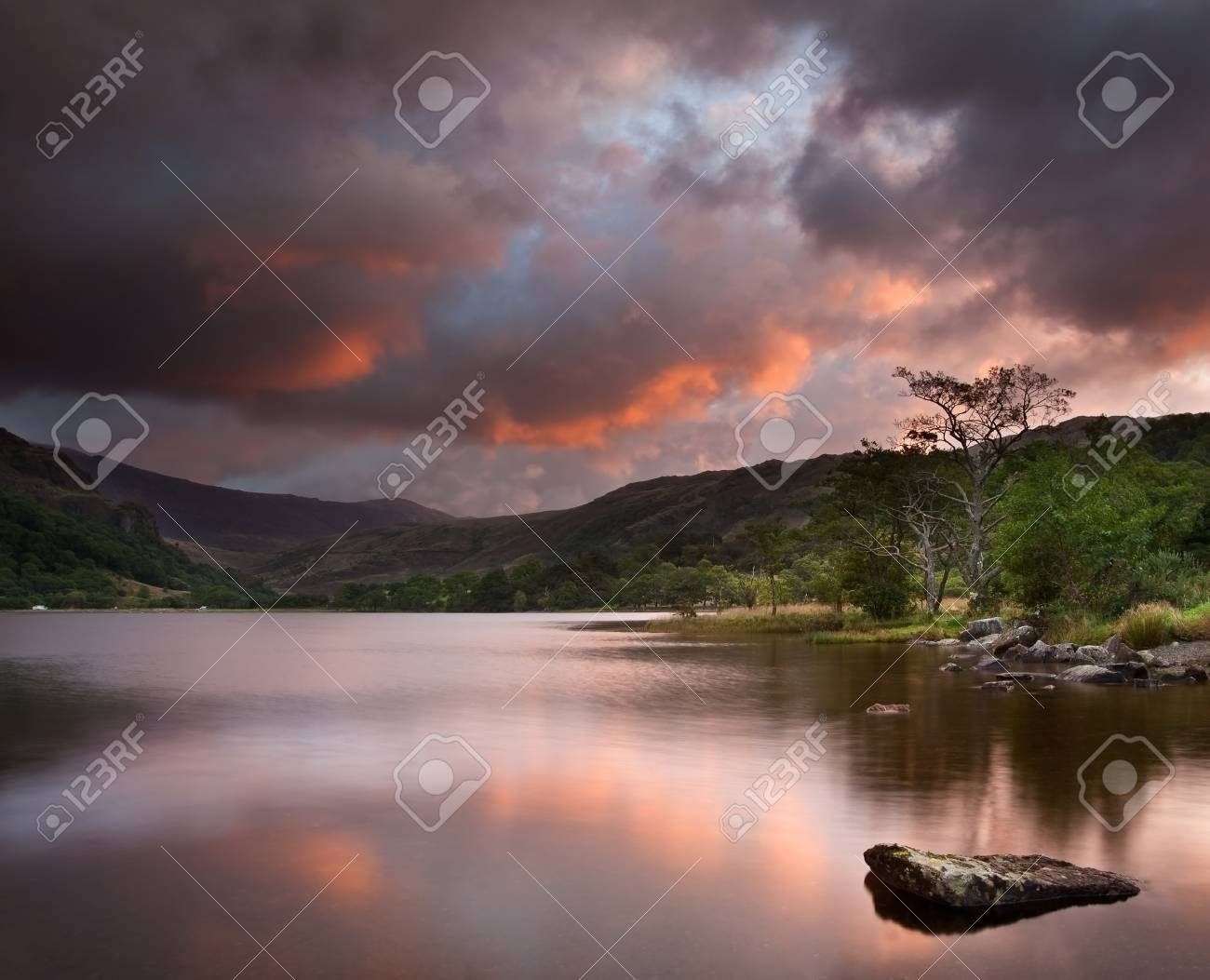 Stunning colorful sunrise over Llyn Gwynant in Snowdonia National Park with Carneddau mountain range in distance Stock Photo - 15778931