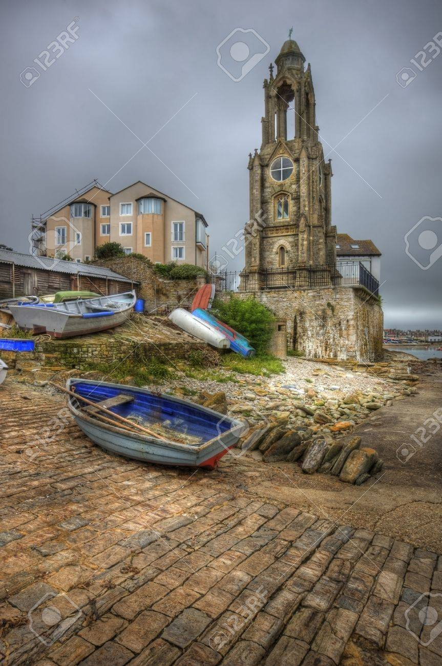 Old seaside town with lookout tower on seashore and rowing boat in foreground Stock Photo - 15887449