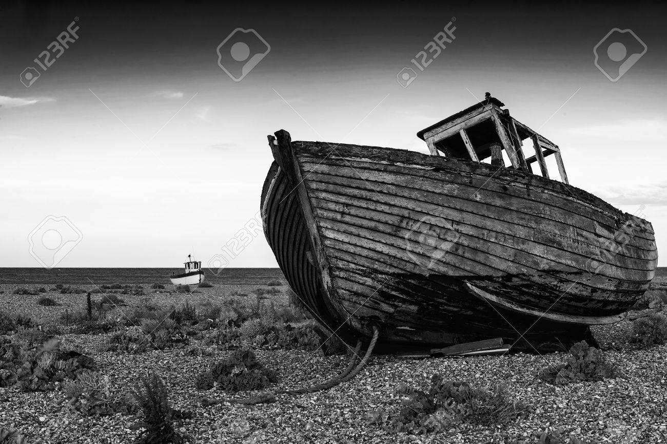 Abandoned fishing boat on shingle beach landscape at sunset black