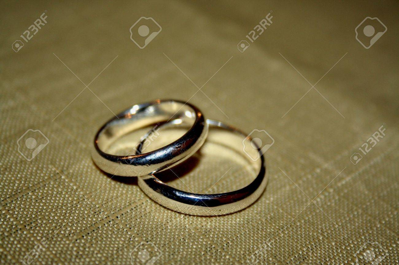 White Gold Wedding Rings Over A Gold Table Cloth Stock Photo