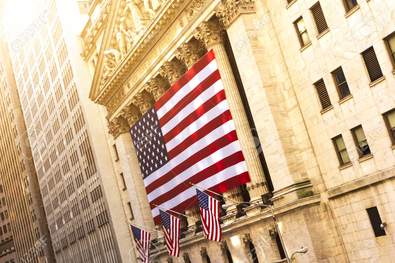 Famous Wall street and the building in New York, New York Stock Exchange with patriot flag - 82008019