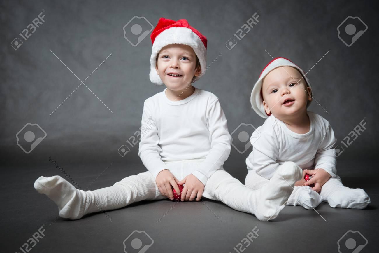 4edbfd1b6e2 Portrait Of Two Cute Boys In Santa Hats