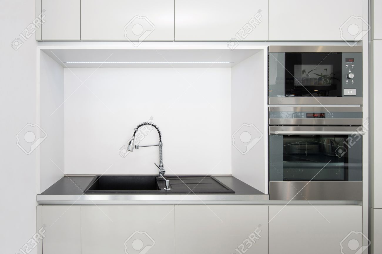archivio fotografico particolare della cucina elettrodomestici da incasso e rubinetto con lavello