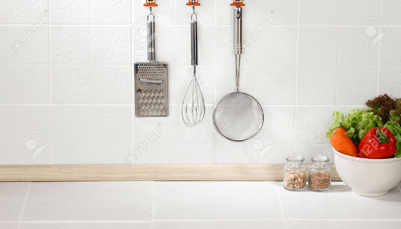 Kitchen Cooking Utensils On Hook Against Tile Wall Stock Photo   15772065