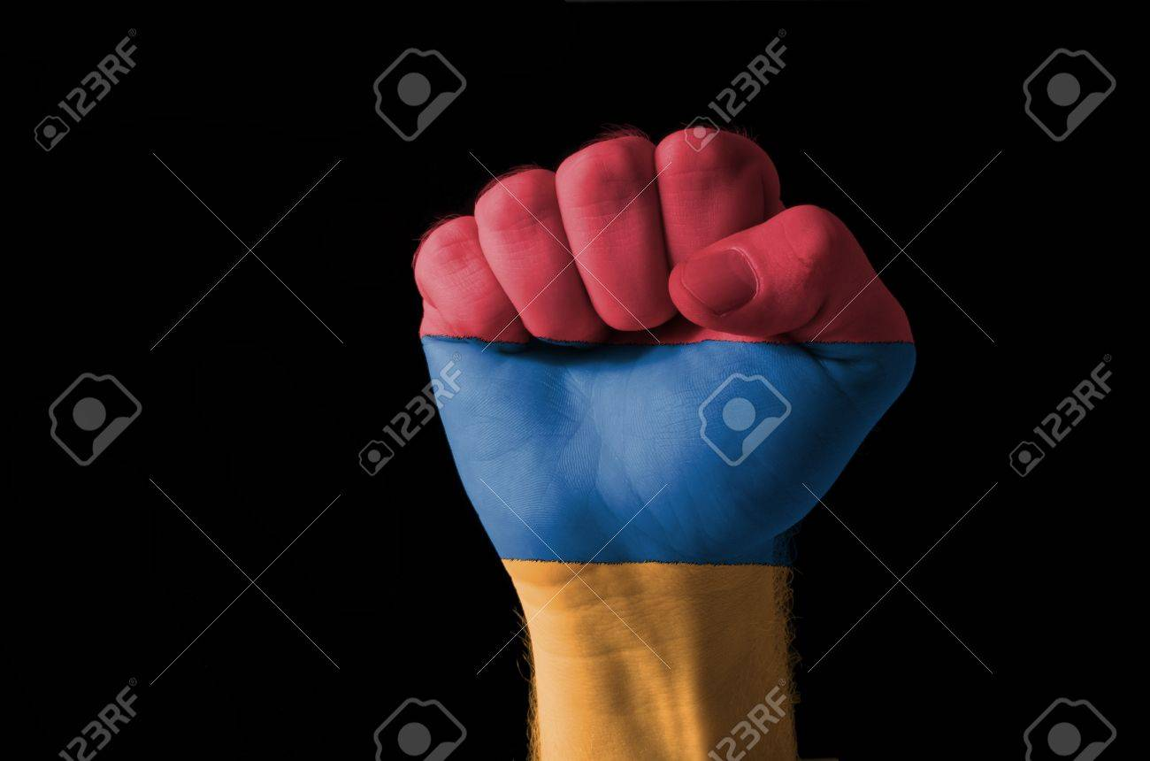 Low key picture of a fist painted in colors of armenia flag Stock Photo - 11063256