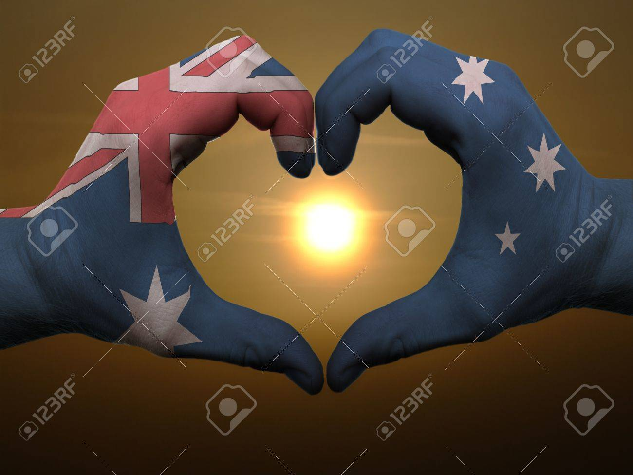 Gesture made by australia flag colored hands showing symbol of heart and love during sunrise Stock Photo - 11112104