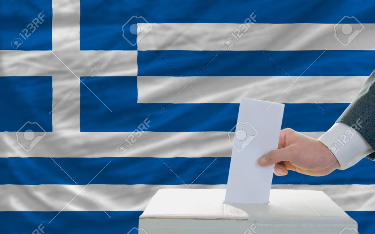 man putting ballot in a box during elections in greece in fornt of flag Stock Photo - 11493661