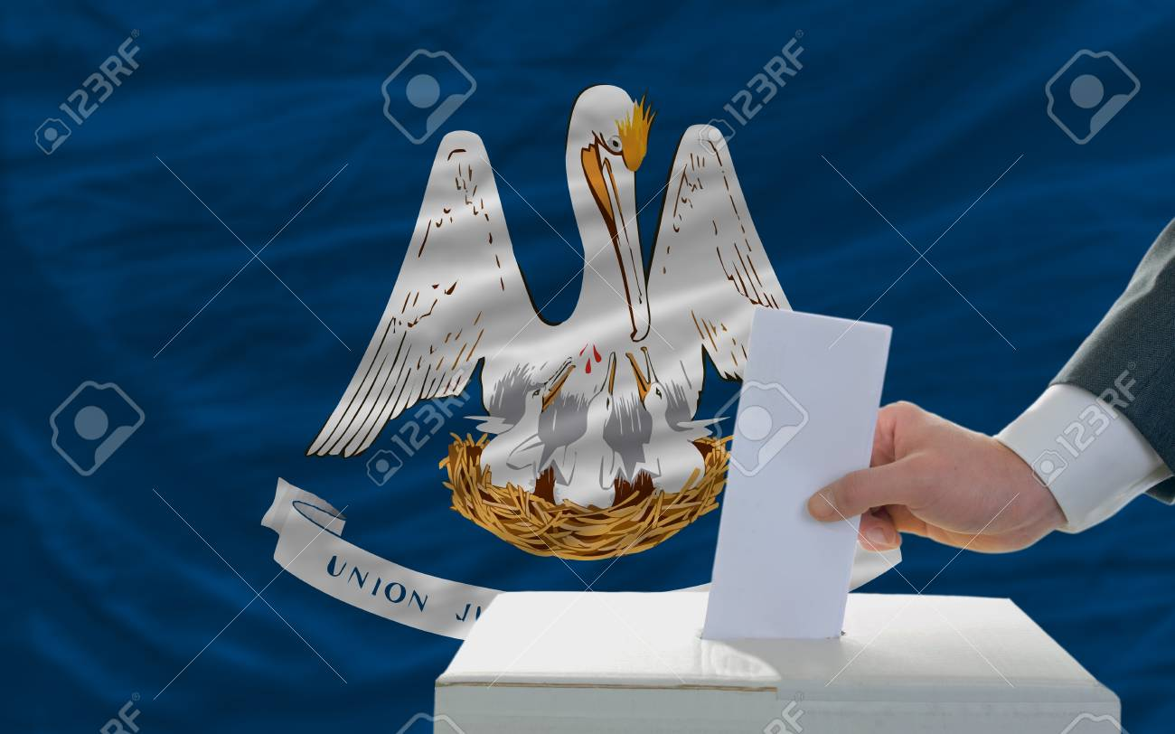 man putting ballot in a box during elections  in front of flag american state of louisiana Stock Photo - 11982842