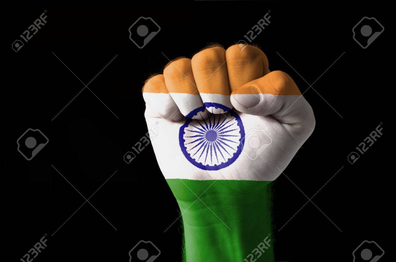 low key picture of a fist painted in colors of india flag stock