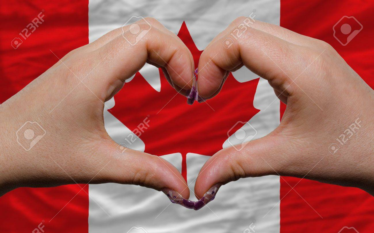 Gesture made by hands showing symbol of heart and love over national canada flag Stock Photo - 12478879