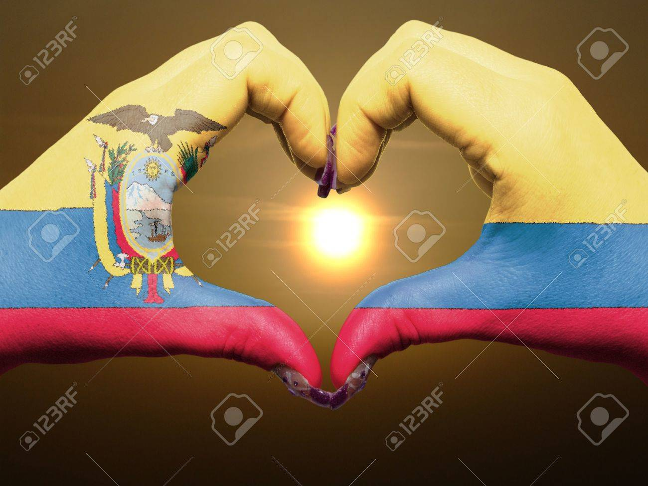 Gesture made by ecuador flag colored hands showing symbol of heart and love during sunrise Stock Photo - 12981544
